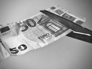 Käärid lõikavad rahatähte.